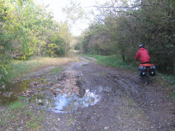 Riding along muddy, dirt road on official bike route