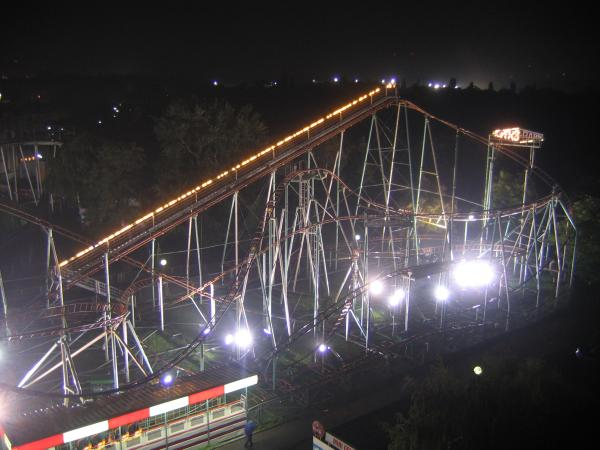 View of amusement park roller coaster from ferris wheel